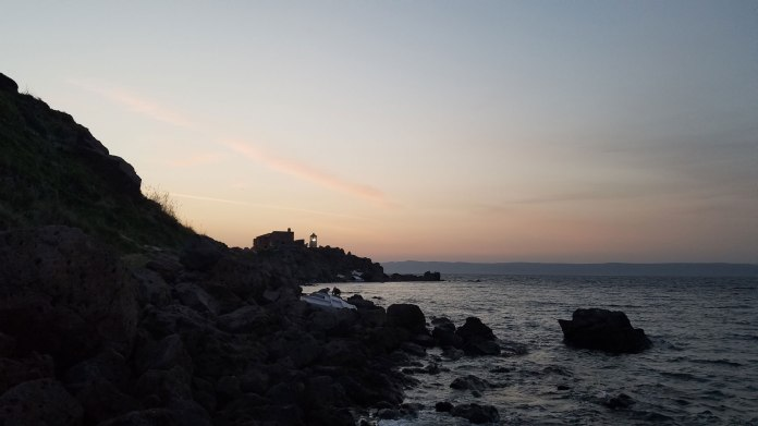 A photo of Koraas lighthouse silhouetted against the setting sun.
